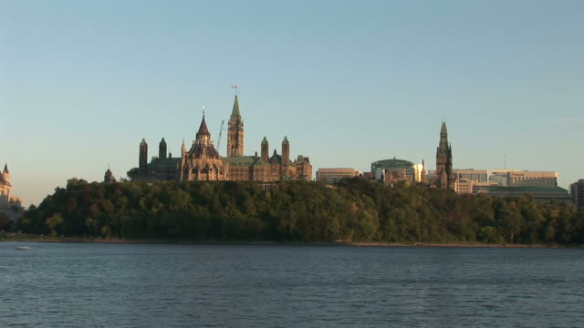 Wide shot of Parliament Hill from Ontario river in Ottawa Canada