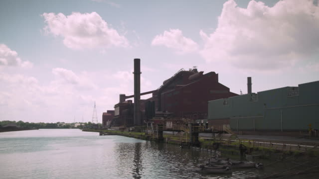 wide shot of part of a large manufacturing complex situated on a river, dearborn, michigan, usa. - dearborn michigan stock videos and b-roll footage