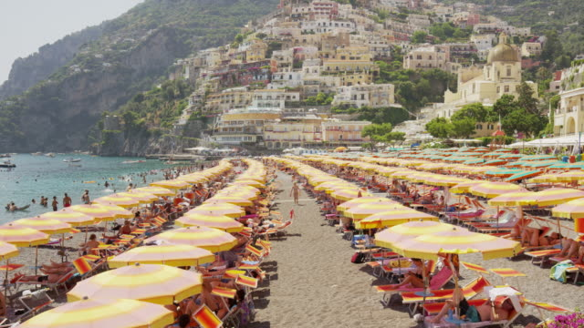 Wide shot of people at urban waterfront beach with beach umbrellas / Positano, Campania, Italy