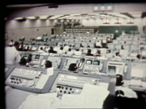 wide shot of people + control panels in mission control - sala di controllo video stock e b–roll