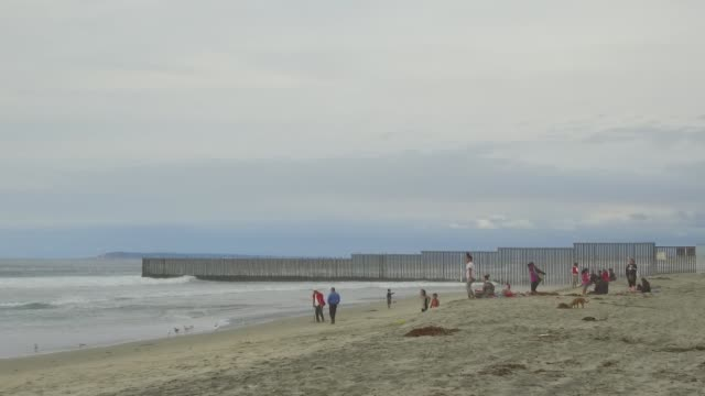 Wide shot of people lounging and playing at the shorline near the Mexico/US Border in Tijuana Mexico on October 31 2017 Photographer Dan Acker