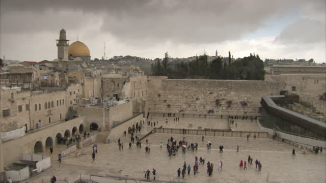 wide shot of people milling around the western wall plaza and standing in front of the western wall, jerusalem. - wallfahrt stock-videos und b-roll-filmmaterial