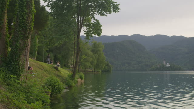 Wide shot of people relaxing at lake / Bled, Slovenia