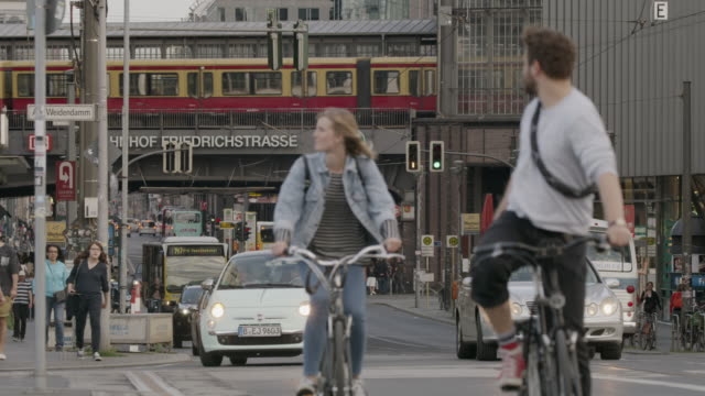 Wide shot of people riding bicycles in busy city intersection / Berlin, Germany