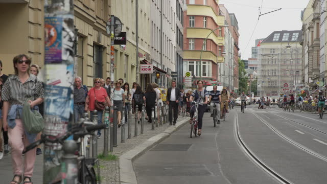 Wide shot of people walking and riding bicycles in city / Berlin, Germany