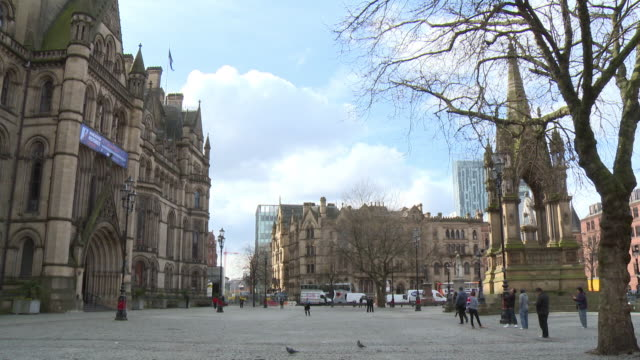 Wide shot of people walking around Albert Square in Manchester, UK.