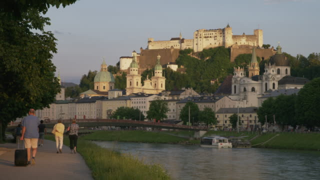 Wide shot of people walking near urban river / Salzburg, Austria