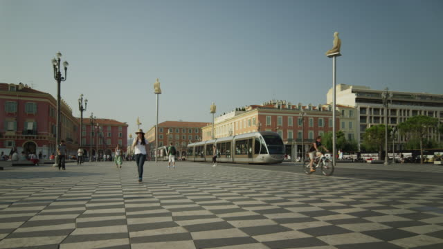 vidéos et rushes de wide shot of people walking through place massena / nice, france - tramway