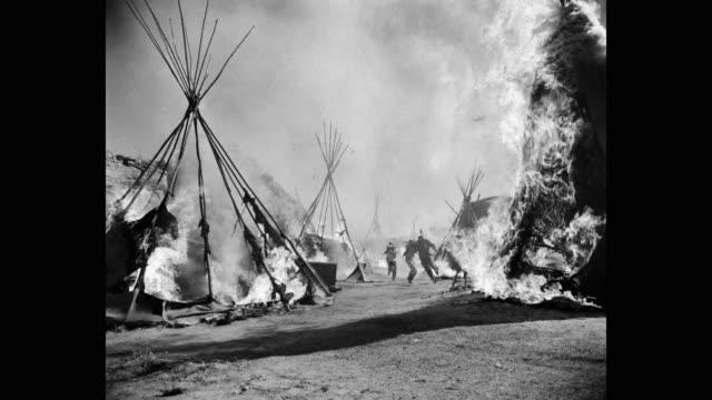 vídeos y material grabado en eventos de stock de wide shot of people wrapped in blanket and running through burning teepee tents - western usa