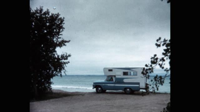wide shot of pickup truck with camper arriving on beach - camper van stock videos & royalty-free footage