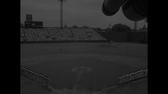 wide shot of players lined up on ball field at griffith stadium for 1956 major league baseball all star game / cutaway to photographers / close up of... - チーム写真点の映像素材/bロール