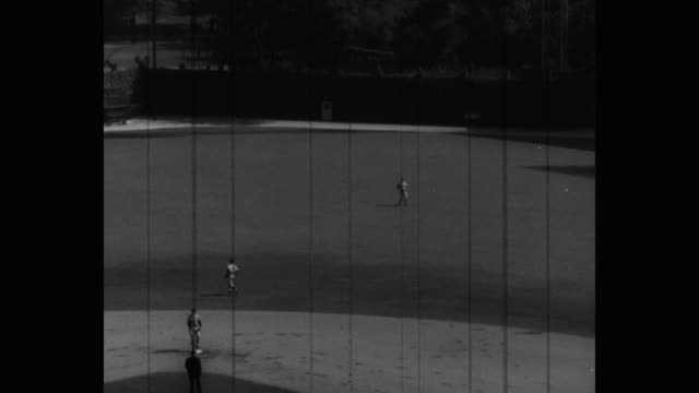 wide shot of players playing baseball on field - baseballmannschaft stock-videos und b-roll-filmmaterial