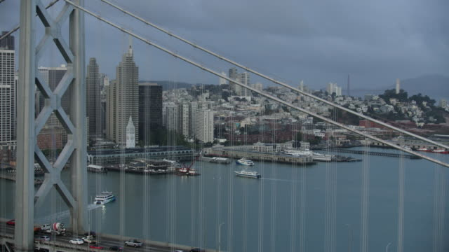 wide shot of port of san francisco revealing through the cables of the san francisco–oakland bay bridge - baia di san francisco video stock e b–roll