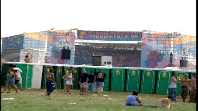 vídeos y material grabado en eventos de stock de wide shot of porta potties and stage at woodstock '99 - 1999