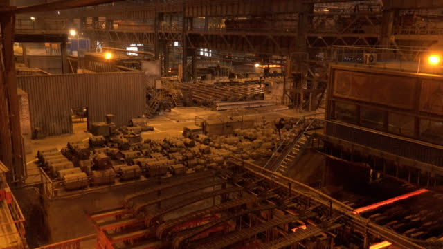 wide shot of production process in metallurgical factory floor - schwer stock-videos und b-roll-filmmaterial