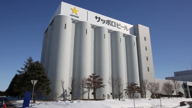 Wide shot of Raw material tanks stand at the Sapporo Breweries Ltd factory in Eniwa Hokkaido Japan on Monday Feb 17 Wide shot a truck drive past raw...