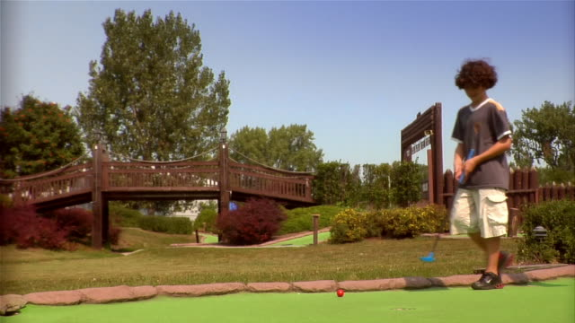 wide shot of red golf ball on putting green at mini golf course / father and son walking up to ball / father showing son how to putt - minigolf stock-videos und b-roll-filmmaterial