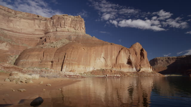 wide shot of reflection of rock formation in lake / lake powell, utah, united states - lake powell stock videos & royalty-free footage