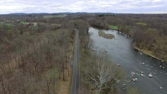 vidéos et rushes de wide shot of road running parellel to river in upstate new york - arbre sans feuillage