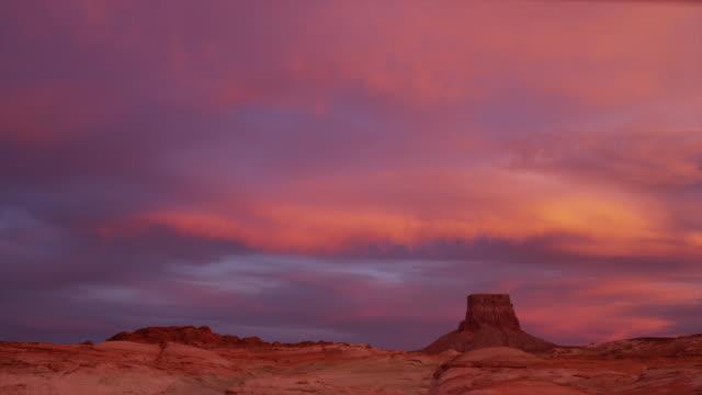vídeos de stock, filmes e b-roll de wide shot of rock formation in desert under dramatic sky at sunset / lake powell, utah, united states - lake powell