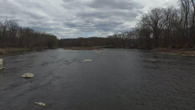 Wide shot of rocky, rushing river flanked by wintery trees in upstate New York on cloudy day