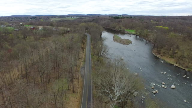 Wide shot of rocky, rushing river flanked by wintery trees in upstate New York