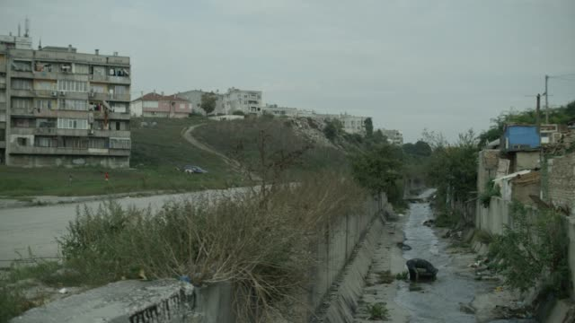 wide shot of roma settlement, tower blocks and open drain - bulgaria stock videos & royalty-free footage