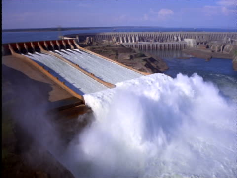 aerial wide shot of rushing water in large hydroelectric dam on river / brazil - dam stock videos & royalty-free footage