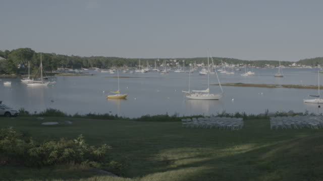 Wide shot of sail boats behind a grass field in Boothbay Harbor