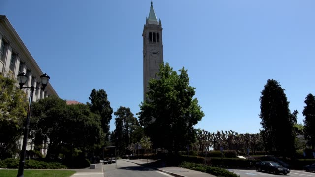 Wide shot of Sather Tower aka the Campanile on the campus of UC Berkeley in Berkeley California on a sunny day with other campus buildings visible...