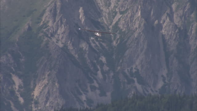Wide shot of seaplane flying with large mountains and forest in background