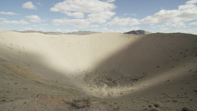 wide shot of sedan crater explosion crater in the desert at nevada test site - bomb stock videos and b-roll footage
