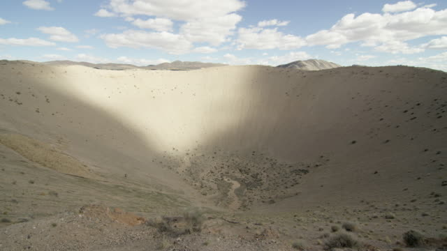 wide shot of sedan crater explosion crater in the desert at nevada test site - sedan stock videos & royalty-free footage