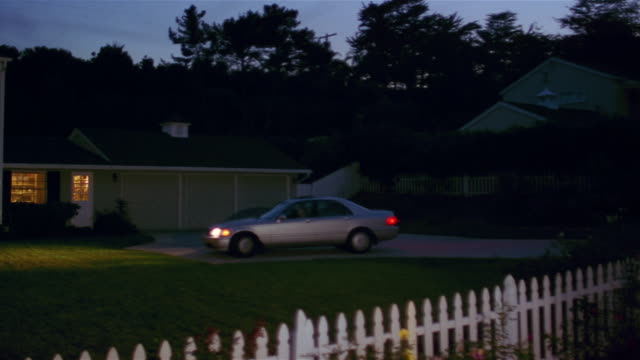 Wide shot of sedan pulling into driveway at night / pan to front of suburban house with lights on / Santa Barbara, California