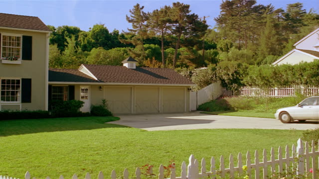 Wide shot of sedan pulling into driveway / pan to front of suburban house with white picket fence / Santa Barbara, California