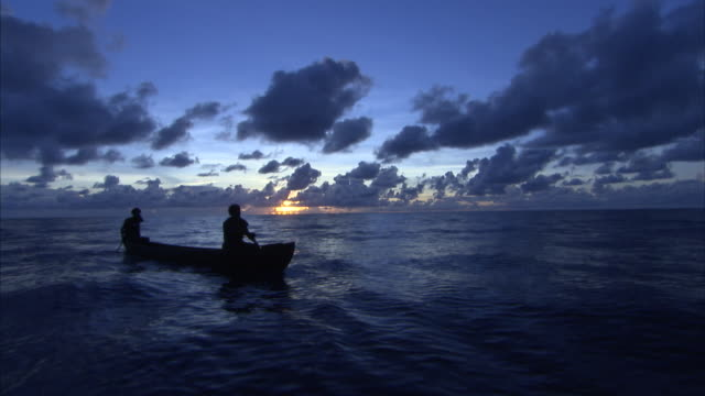 Wide shot of silhoetted canoe paddling across open ocean