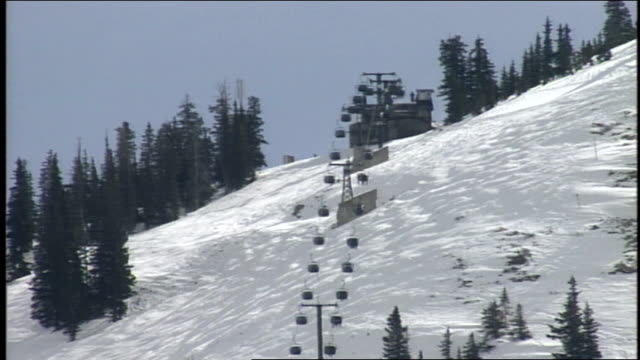 wide shot of ski lifts moving up and down mountain in butte colorado - スキーウェア点の映像素材/bロール