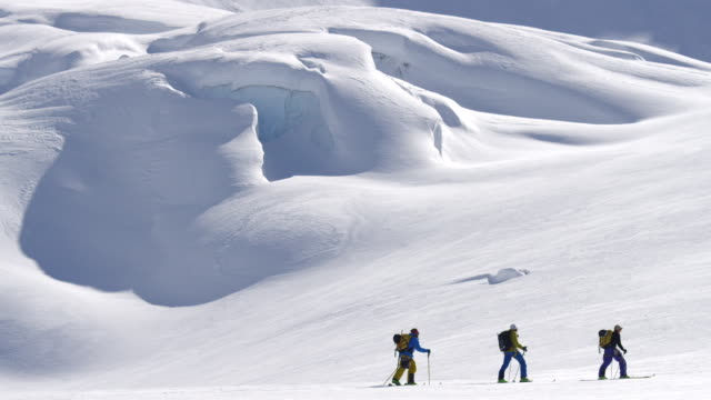 Wide shot of skiers touring across glacier in Alaska NO