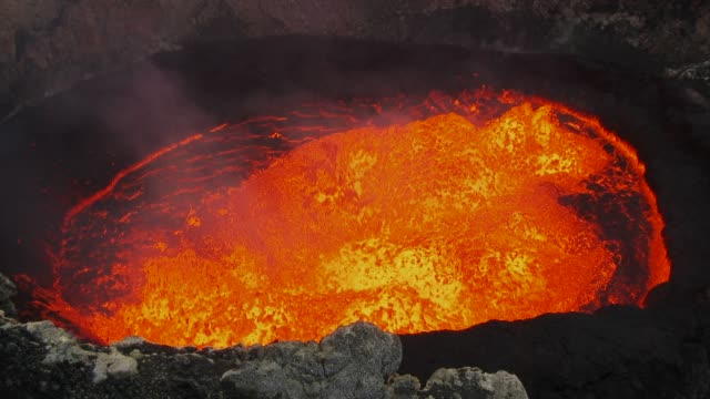 wide shot of smoke rising from a lava lake - vulkanausbruch stock-videos und b-roll-filmmaterial