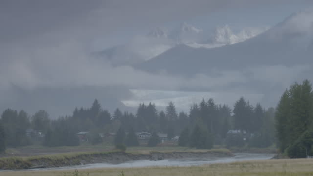 wide shot of snow-covered mountain peaks behind a stream with houses - juneau stock videos and b-roll footage