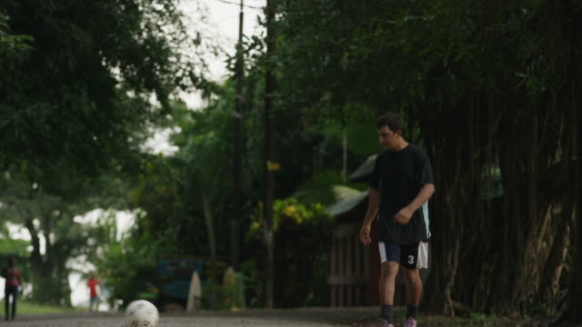wide shot of soccer players passing ball on dirt road / esterillos, puntarenas, costa rica - puntarenas stock-videos und b-roll-filmmaterial