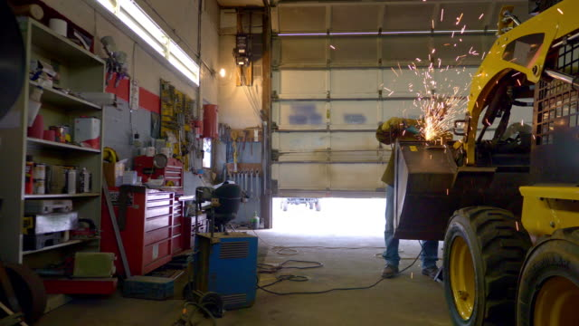 Wide shot of sparks flying as a man grinds heavy equipment in a repair shop