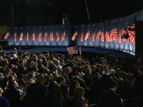 vidéos et rushes de wide shot of stage filled with american flags, with the crowd awaiting the victory speech of president-elect barack obama - président