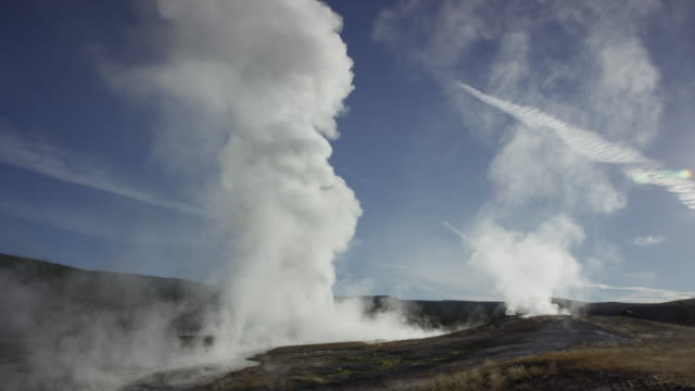 stockvideo's en b-roll-footage met wide shot of steam rising from old faithful geyser / yellowstone national park, wyoming, united states - old faithful geiser