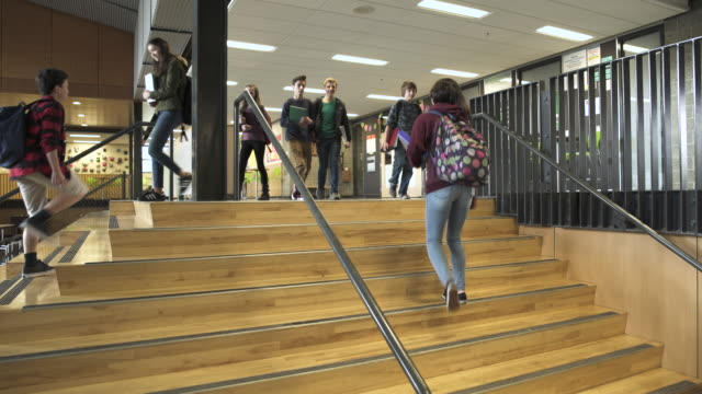 wide shot of students passing-by on the stairs - junior high stock videos & royalty-free footage