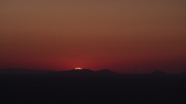 wide shot of sun rising over mountain range in red sky / oia, santorini, greece - horizont über land stock-videos und b-roll-filmmaterial