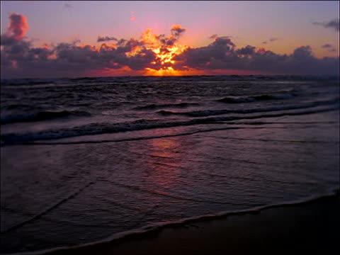 vídeos de stock, filmes e b-roll de wide shot of sunset behind clouds over ocean washing up on beach - céu romântico
