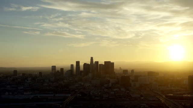 wide shot of sunset over los angeles - schwenk nach unten stock-videos und b-roll-filmmaterial