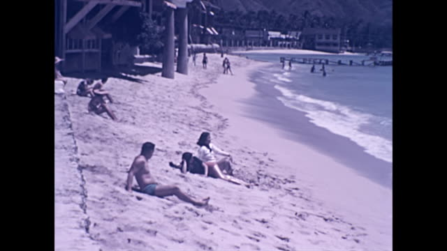 wide shot of surf and outrigger canoe / waikiki beach with royal hawaiian hotel in the background / wide shot of surf / shoreline with sunbathers /... - 1940 1949 stock-videos und b-roll-filmmaterial