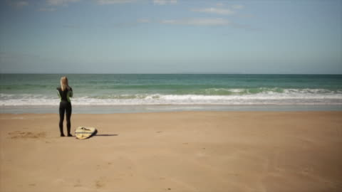 wide shot of surfer looking at surf - channel islands england stock videos & royalty-free footage